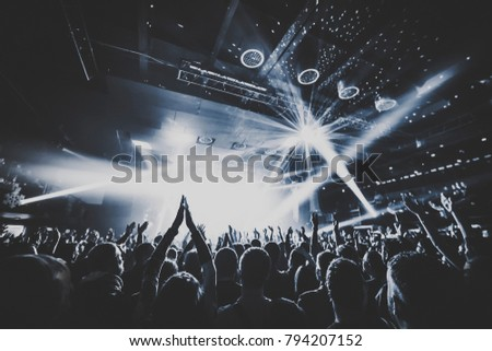 silhouettes of concert crowd in front of bright stage lights. Dark background, smoke, concert  spotlights, disco ball
