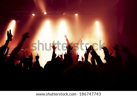 silhouettes of concert crowd in front of bright stage lights singer on stage
