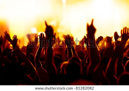 silhouettes of concert crowd in front of bright yellow stage lights