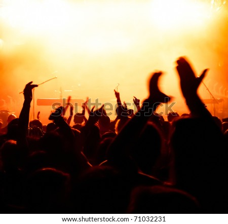 silhouettes of concert crowd in front of bright yellow/white stage lights
