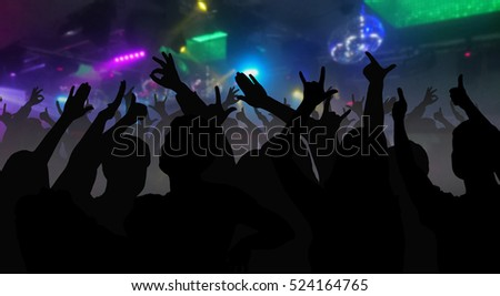 Silhouettes of concert crowd with hands raised at a music festival in nightclub - disco concept