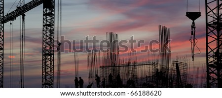 silhouettes of construction workers, construction equipment and elements of a building under construction at Sunset