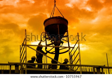Silhouettes of construction workers pouring concrete mix at the building site over sunset sky