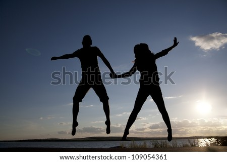 Silhouettes of couple jumping on sunset background