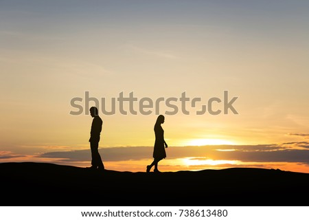 Silhouettes of couple man and woman broken heart. In nature sunset. Love concept.