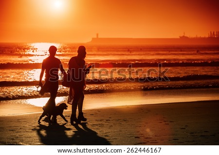 Silhouettes of couple walking dog at sunset beach, lens flare.Copy space, sunset light.Unrecognizable people