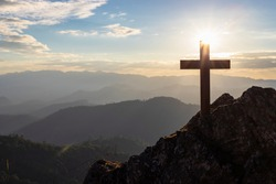 Silhouettes of crucifix symbol on top mountain with bright sunbeam on the colorful sky background