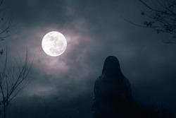 Silhouettes of dry trees against night sky with clouds and Woman stands to watch the full moon in the night alone,nature background