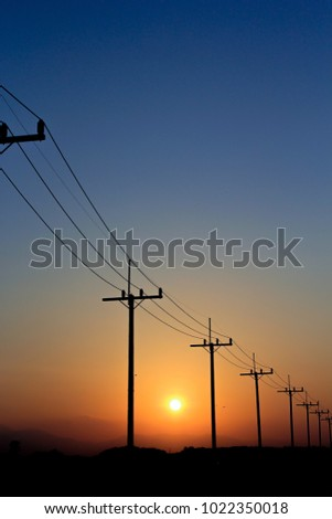 Silhouettes of electricity poles and power lines on sunset. #1022350018