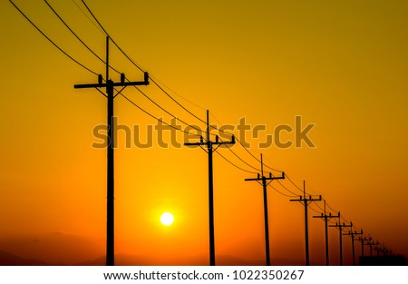 Silhouettes of electricity poles and power lines on sunset.