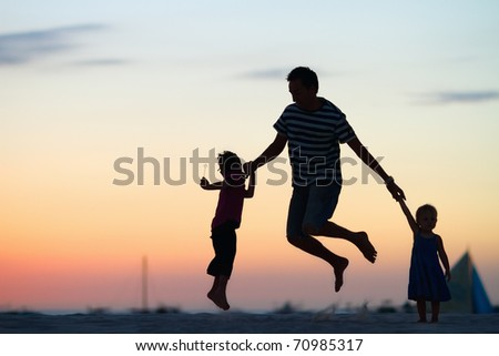 Silhouettes of father and his two kids jumping and having fun on beach at sunset - stock photo