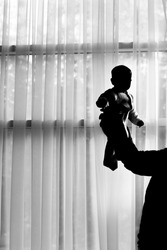 silhouettes of father and little baby playing