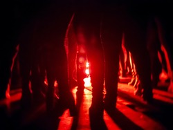 Silhouettes of feet in a nightclub against a bright red lantern in the center with shadows radiating from it on the floor. People stand around the fire