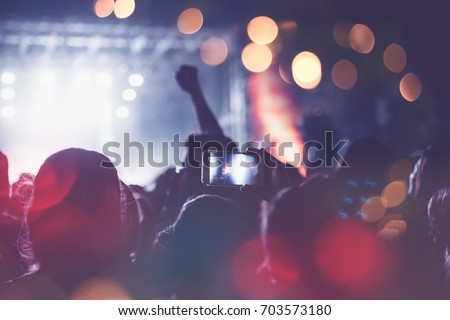 Silhouettes of festival concert crowd in front of bright stage lights. Unrecognizable people and colorful effects.