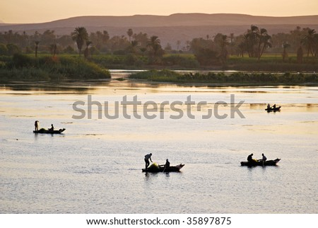 silhouettes of fishermen on traditional boats at twilight