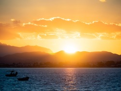 Silhouettes of fishing boats in the Mediterranean in the last rays of the setting sun. Scenic yellow sunset on a cloudy sky. The sun sets over the mountains. Hammamet, Tunisia.