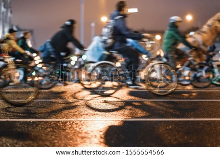 Silhouettes of group colorful cyclists on city road, illumination, abstract, motion blur, bike festival. Concept of modern lifestyle, healthy lifestyle, for background