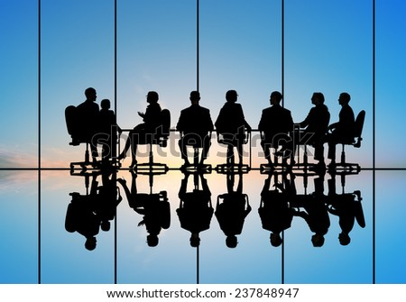 Silhouettes of group of business people against sunset