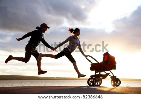 Silhouettes of happy parents are running for a pram