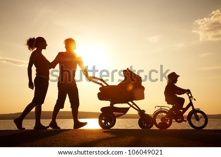 Silhouettes of happy parents having good time with their little children on the seacoast