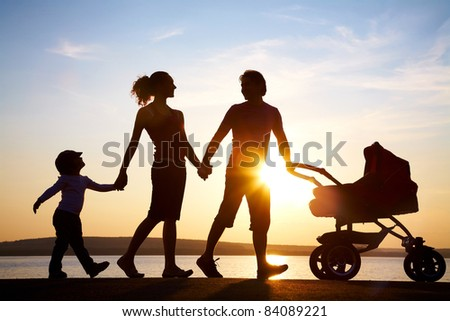 Silhouettes of happy parents walking with child and baby's stroller on the seacoast