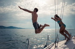Silhouettes of happy people jumping into water from a boat - Friends diving and having fun on a summer vacation