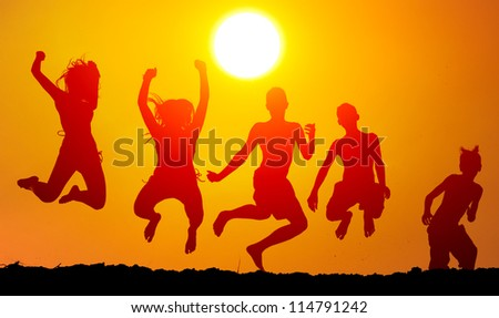 Silhouettes of happy teenagers jumping high in the air on sunny summer day.
