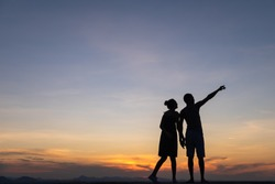 Silhouettes of happy young couple against the sunset sky.point