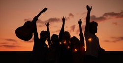 Silhouettes of happy young people with guitar having fun and dancing with hands up during outside party at sunset