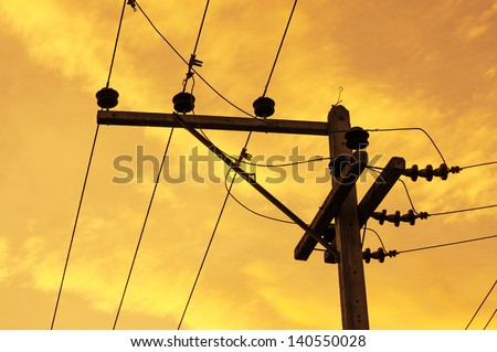 Silhouettes of High voltage pole and power lines on sunset