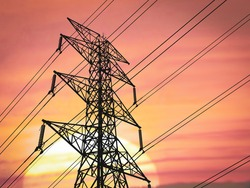Silhouettes of high voltage poles and power lines It has a complex steel structure, it is strong and durable. high-voltage power lines at sunset, high voltage electric transmission tower.