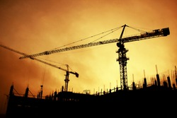 Silhouettes of huge tower cranes on the background of the construction site and building frame, behind which is an orange sunset
