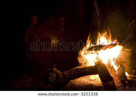 Silhouettes of indigenous drummers sitting near the flame. India
