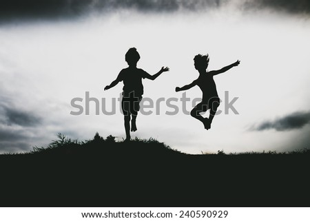 Silhouettes of kids jumping from a cliff