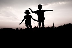 Silhouettes of kids jumping off a cliff at sunset. Little boy and girl jump raising hands up high. Brother and sister having fun in summer. Friendship, freedom concept. Twins on vacation in mountains.