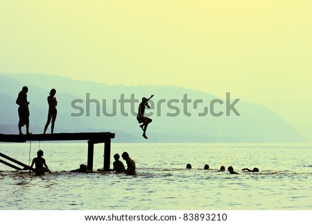 Silhouettes of kids who jump off dock on the lake at sunset. - stock photo