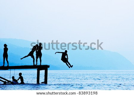 Silhouettes of kids who jump off dock on the lake.Blue toned.
