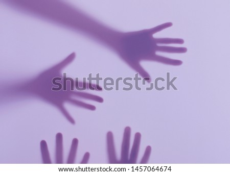 Silhouettes of male and female hands. Conceptual scene. Male and female hands behind a frosted glass.