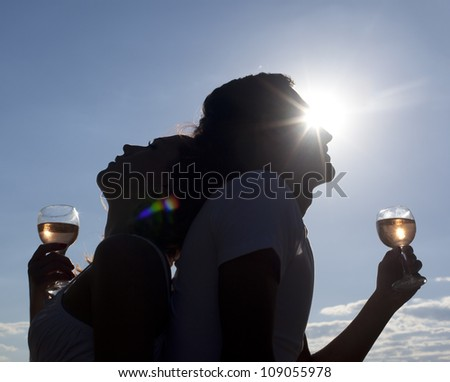 Silhouettes of Man and woman clinging glasses of champagne at sunset dramatic sky background
