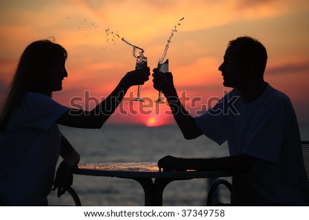 silhouettes of man and woman splash out drink from glass on sea sunset. focus on man