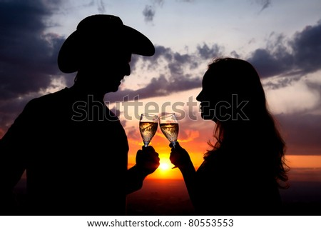 Silhouettes of Man in cowboy hat and woman clinging glasses of champagne at sunset dramatic sky background