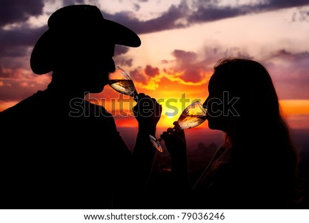 Silhouettes of Man in cowboy hat and woman drinking champagne from wine glasses at sunset dramatic sky background