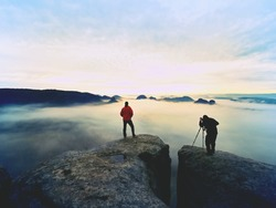 Silhouettes of man photographers. Men on mountain. Peak  with two men taking photos in autumn morning sunrise