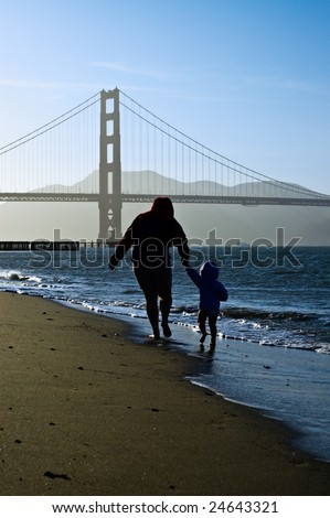 Silhouettes of mom and an infant daughter walking barefoot to silhouetted Golden Gate Bridge on a sunny but cold spring day.