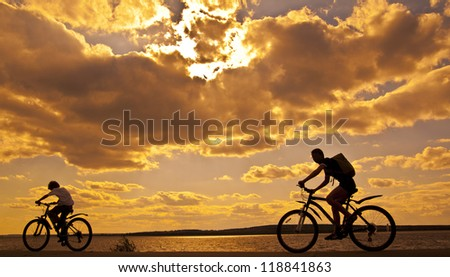 silhouettes of mother and child on bicycle against sunset sky