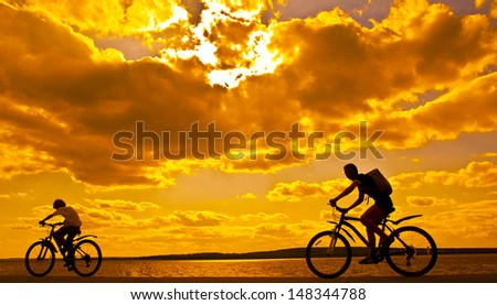 silhouettes of mother and child on bicycle against sunset sky Copy space for inscription