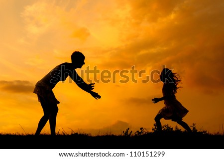 Silhouettes of mother and daughter meeting on the meadow at summer sunset.