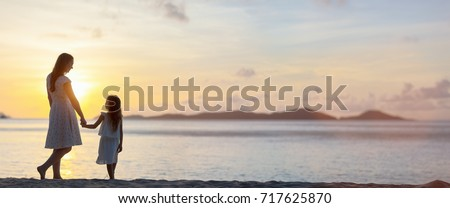 Silhouettes of mother and daughter walking along tropical beach during sunset, panorama with copy space perfect for banners