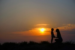 Silhouettes of mother and little daughter at sunset.
