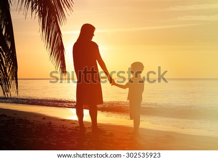 silhouettes of mother and son holding hands at sunset sea
